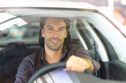 Guy Smiling Behind the Wheel of Car